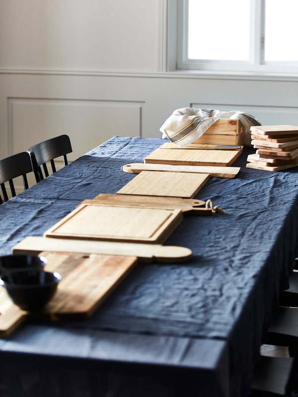 A table covered in blue cloth with a line of different types of wooden chopping boards including PROPPMÄTT along the middle.