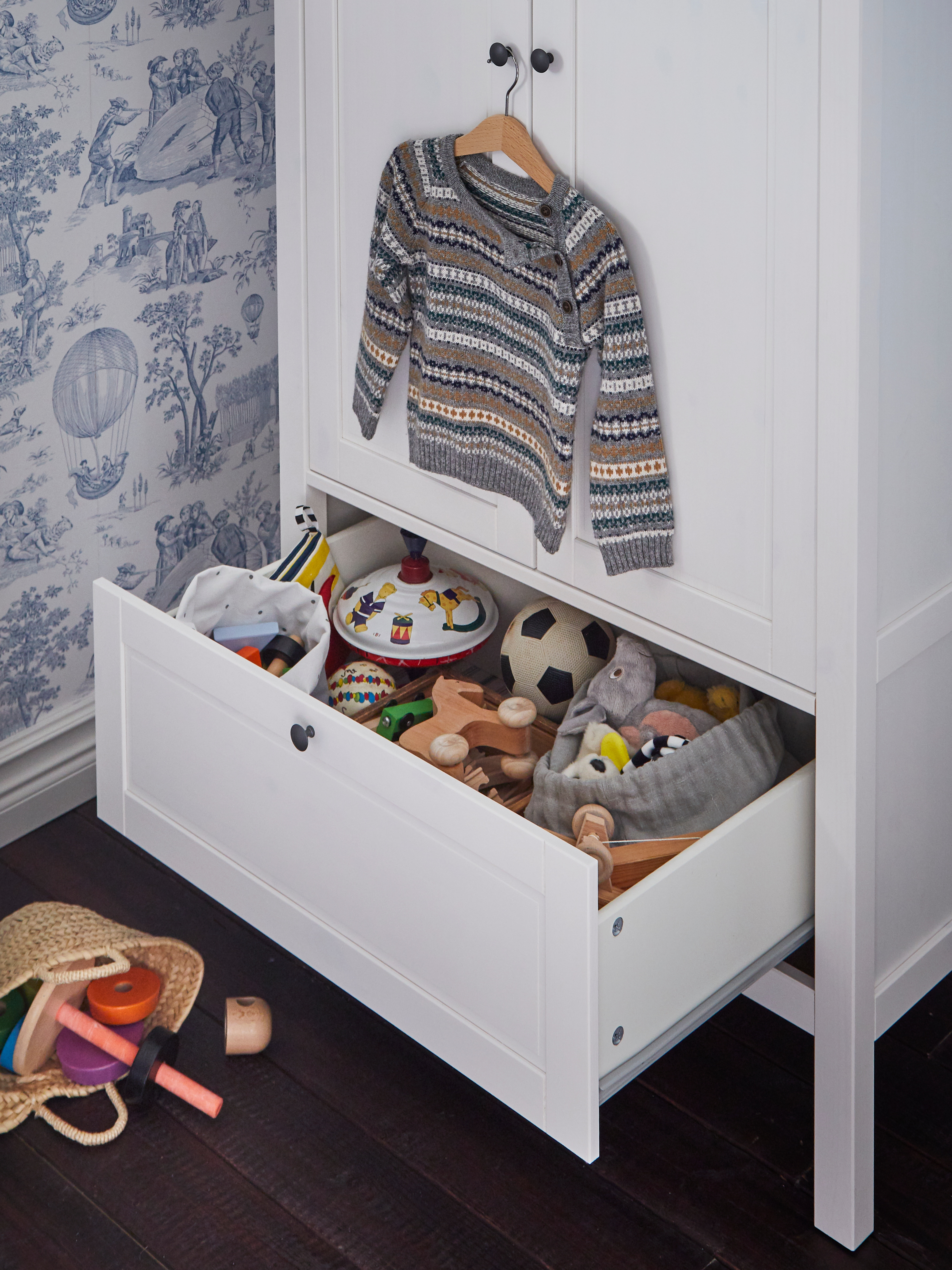 A traditional white SUNDVIK wardrobe with a low open drawer holding toys and a child's sweater hanging above on a door knob.