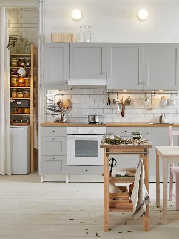 Белая кухня КНОКСХУЛЬТ с настенным и напольными шкафами. На плите стоит кастрюля, в духовке пирог.