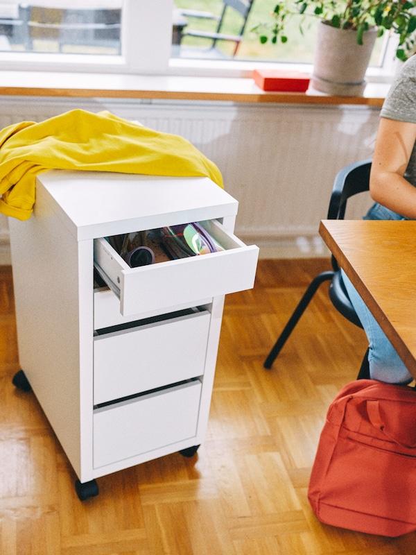 Una cassettiera bianca con rotelle, su cui è appoggiata una giacca gialla, accanto a una scrivania in una stanza.