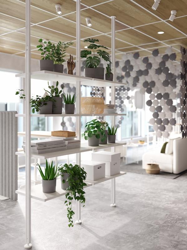 Scaffale formato da ripiani e montanti bianchi usato come divisorio, con piante in vaso, libri e contenitori bianchi.