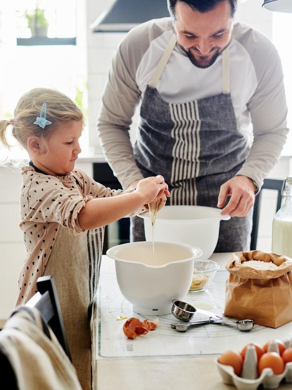 Pai e filha a cozinharem. Menina quebra um ovo para a tigela VISPAD.