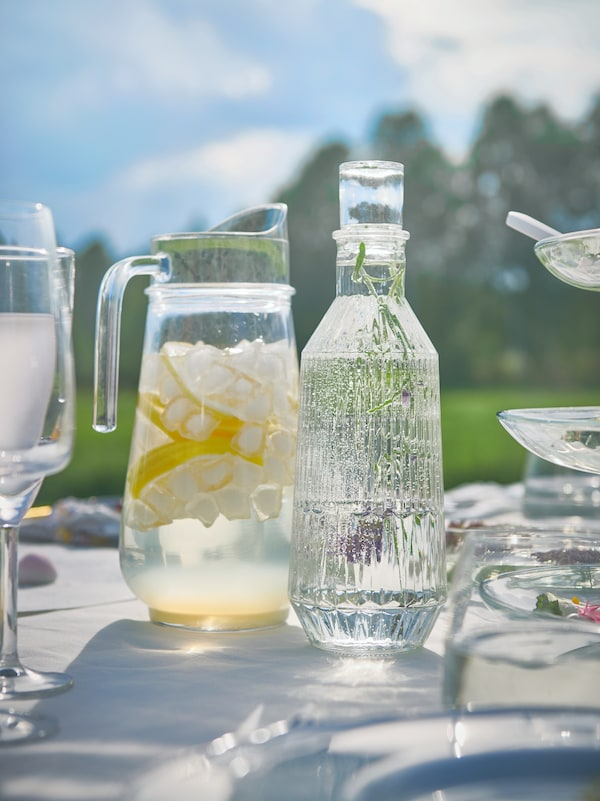 A TILLBRINGARE pitcher and SÄLLSKAPLIG carafe filled with cool, refreshing drinks wait on a table at an outdoor party.