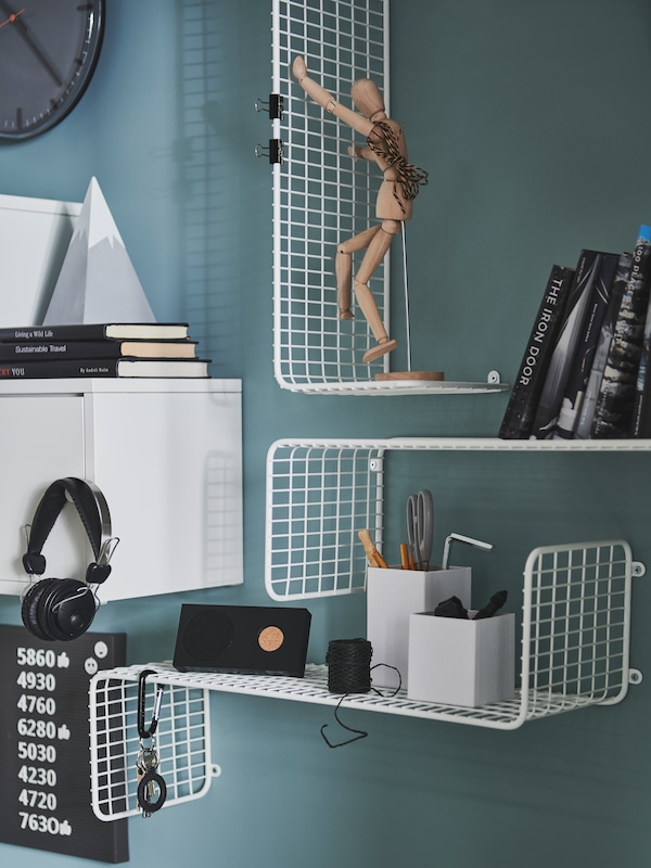 Two SVENSHULT wall shelves are attached horizontally to a wall with another attached vertically, holding an artist's dummy.
