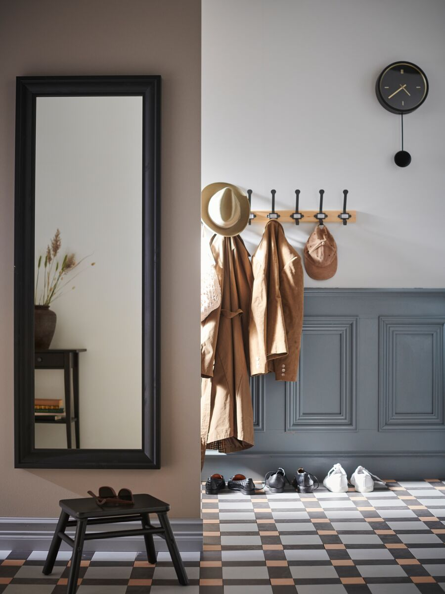 Tiled hallway with TOFTBYN mirror, footstool, hooks with hats and jackets, shoes on the floor and a clock on the wall.