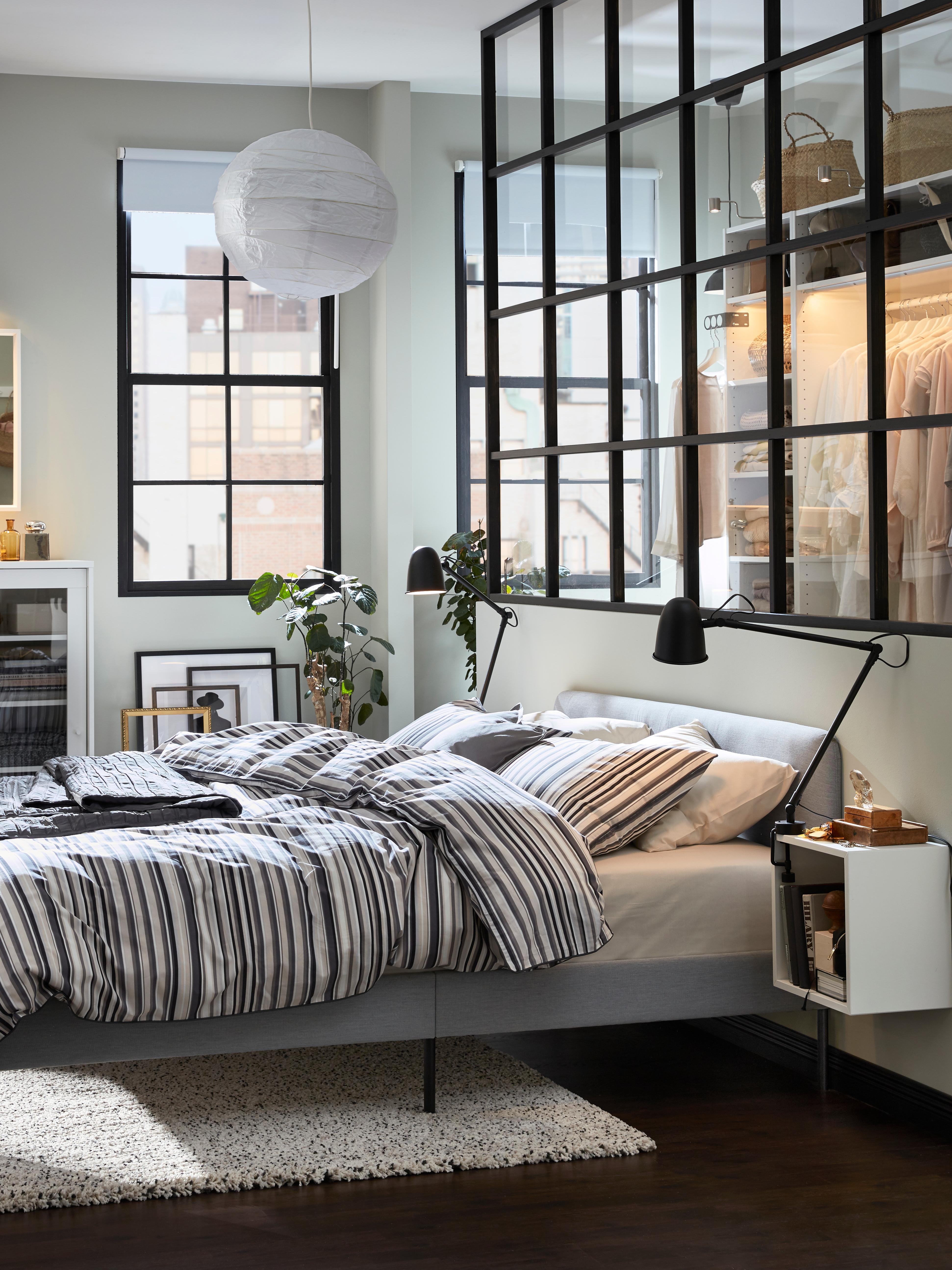 Camera da letto moderna simile a un loft, con struttura letto imbottita SLATTUM grigia, tappeto grigio e lampade nere su mobili a giorno a forma di cubo accanto al letto.