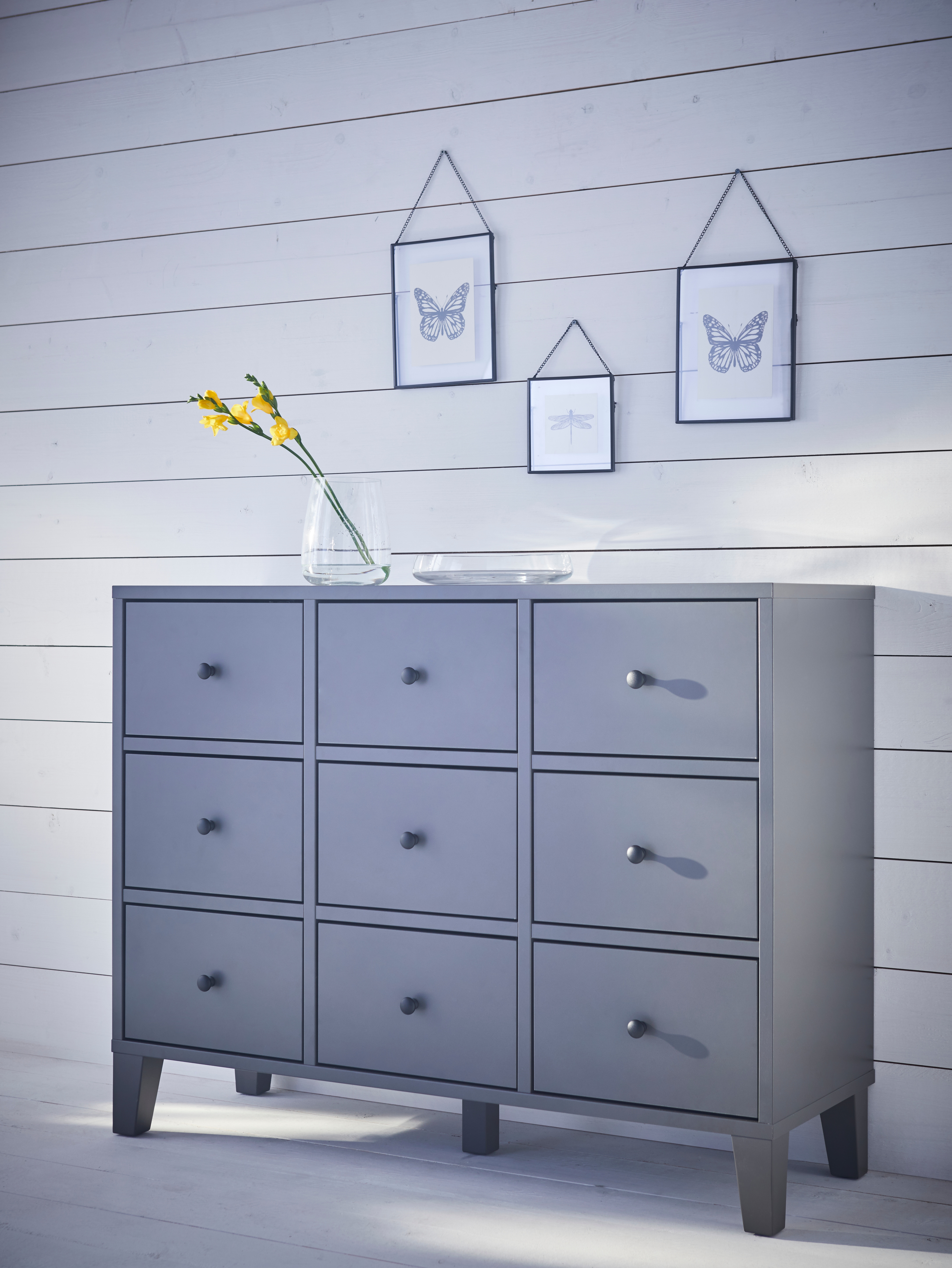 A dark grey BRYGGJA chest of nine drawers is against a plank wall. A glass bowl and yellow flower in glass vase sit on top.