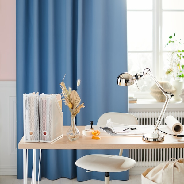 A light wood desk with a white chair and desk accessories, in front of a sunlit window with azure blue curtains.