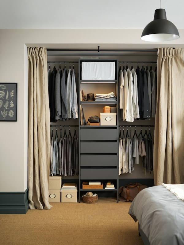 A gray AURDAL storage solution with open shelves and drawers in the middle and hanging shirts on either side.
