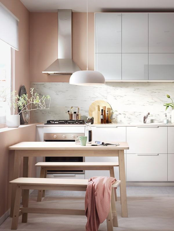 Világos korallszínű helyiség fehér konyha előlapokkal, fa étkezőasztallal és két fa paddal, fehér függőlámpával.