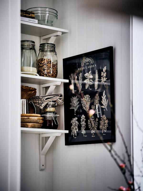 Dans une alcôve blanche, trois étagères murales montées l'une au-dessus de l'autre accueillant des bocaux d'aliments, saladiers en verre, livres et serviettes.