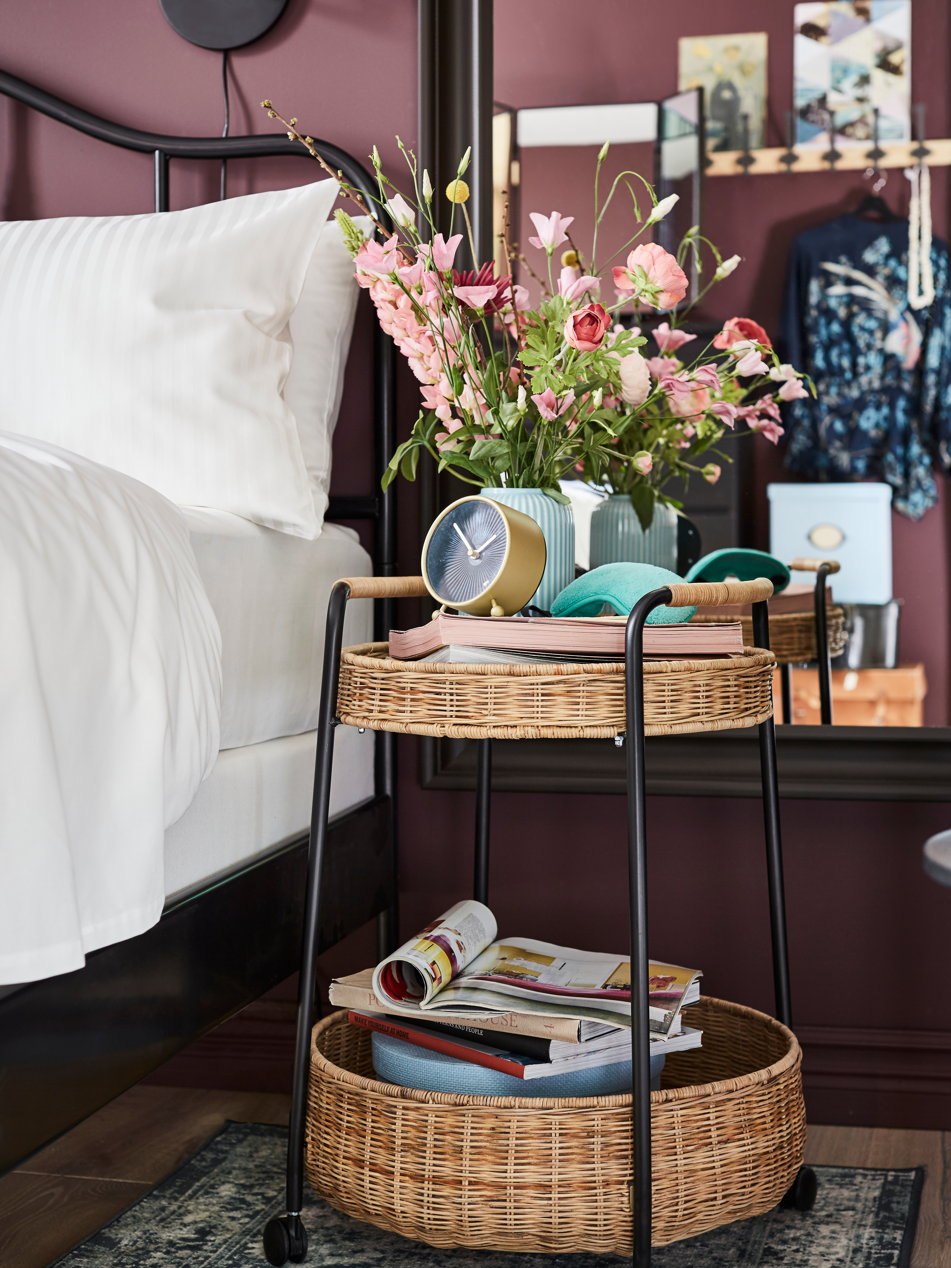 Bedroom with steel bed frame, quilt cover and pillowcases, trolley made of steel and rattan, table clock, rack with hooks.