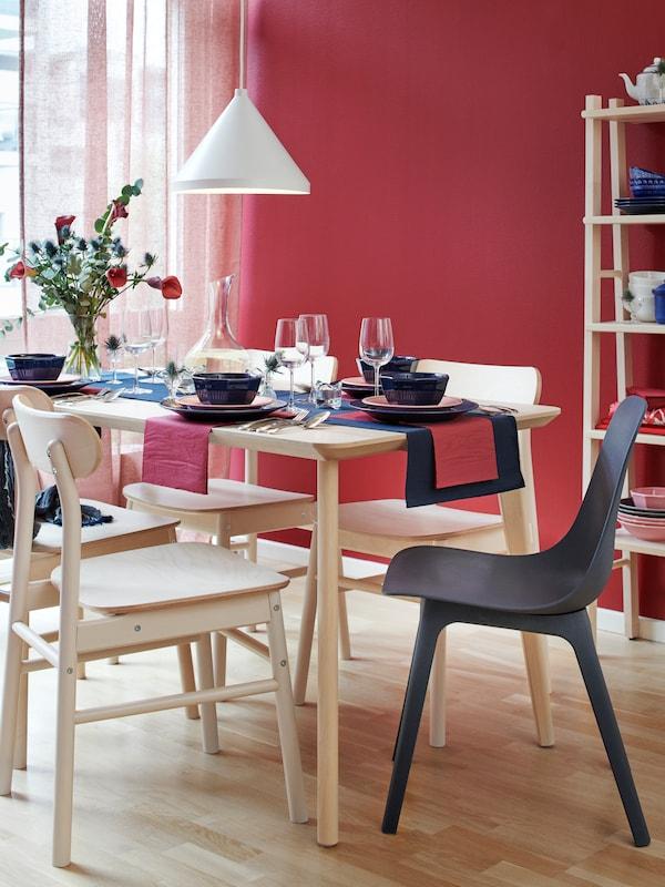 Ruokailutila, jossa on punainen seinä ja iso ikkuna. Tilassa on puinen LISABO-pöytä, jonka ympärillä on neljä puista RÖNNINGE-tuolia.