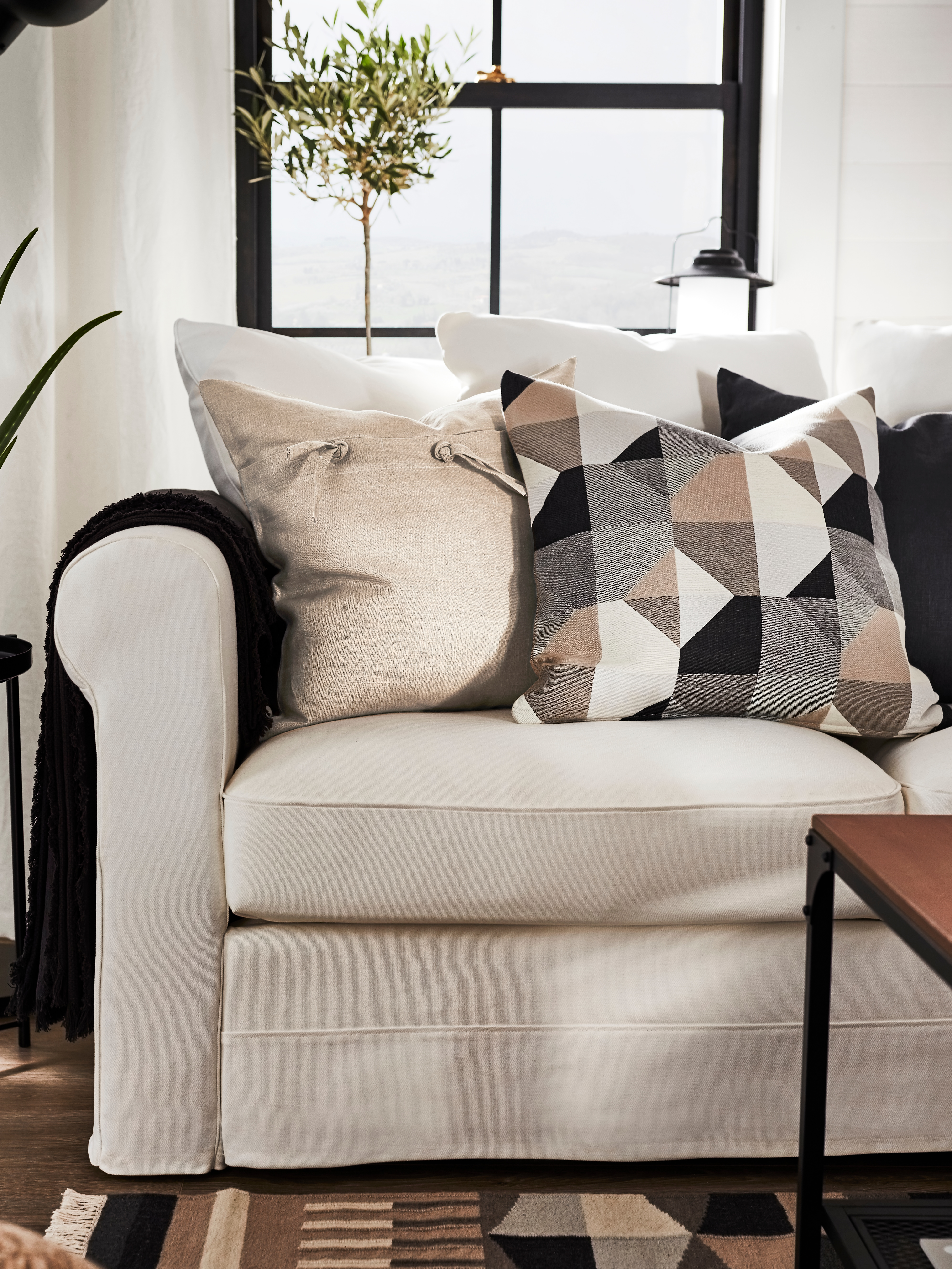 Un divano bianco ha cuscini quadrati con varie fodere, tra cui una fodera SVARTHÖ beige con motivo geometrico.