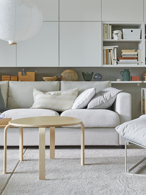 A bright living room with a white sofa, many white wall-mounted cabinets and a round, white pendant lamp.