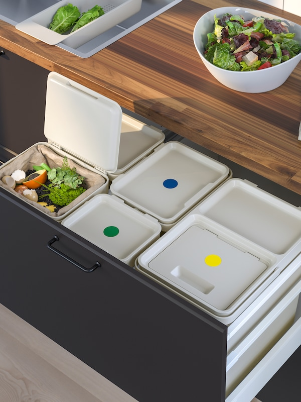 HÅLLBAR recycling bins inside an open kitchen drawer. On the countertop above is a bowl of salad.