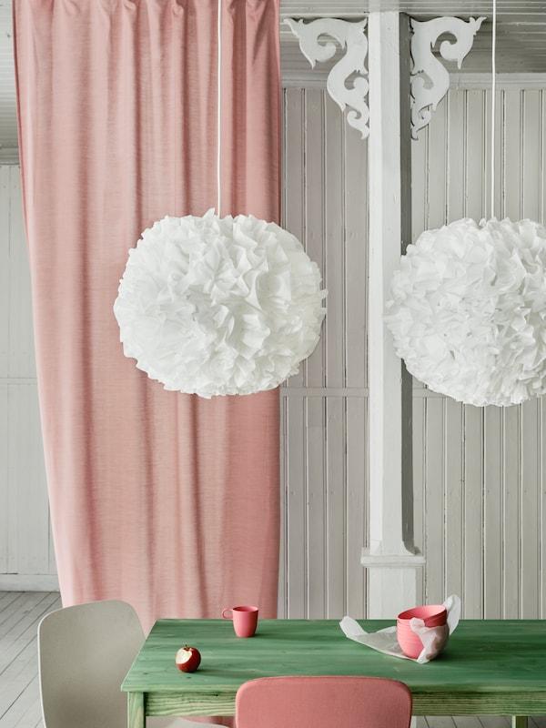 Dvě závěsné lampy VINDKAST ve tvaru bílých bambulek visí nad zeleným stolem s růžovým závěsem u v pozadí.