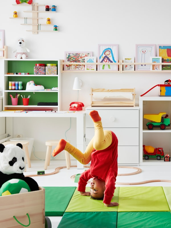 A child does a headstand on a green PLUFSIG folding gym mat in front of a wall with storage, toys and drawings.