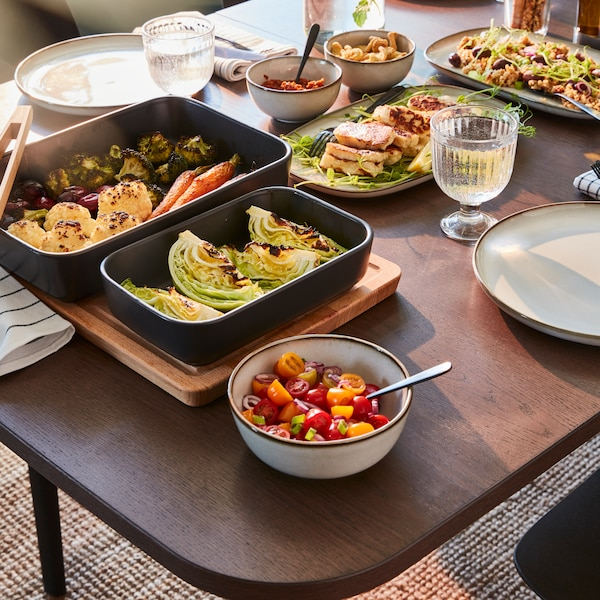 A wooden dining table with two black oven dishes with vegetables, bowls with chopped tomatoes, two plates, and more.