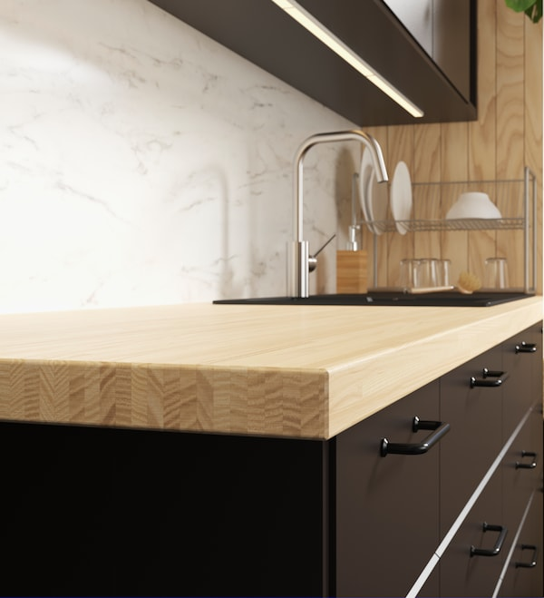 A close up of a kitchen with wooden countertops and black cabinets and pulls.