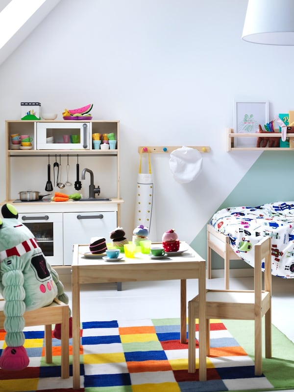 Zwei Kinder sitzen sich an einem Tisch gegenüber und spielen mit BYGGLEK Schachteln und LEGO. Eine große BYGGLEK Schachtel liegt unter dem Tisch.