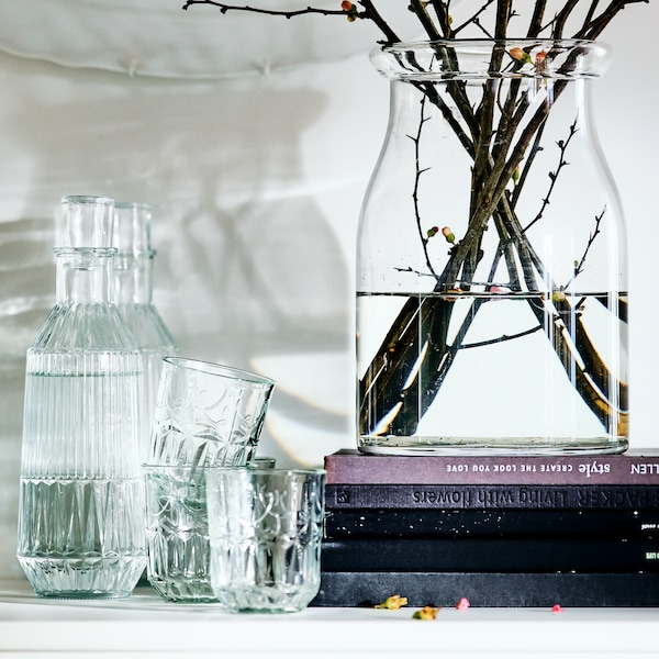 Un vase BEGÄRLIG contenant de l'eau et des branches, sur une tablette accueillant une carafe et des verres, devant un mur orné d'assiettes.