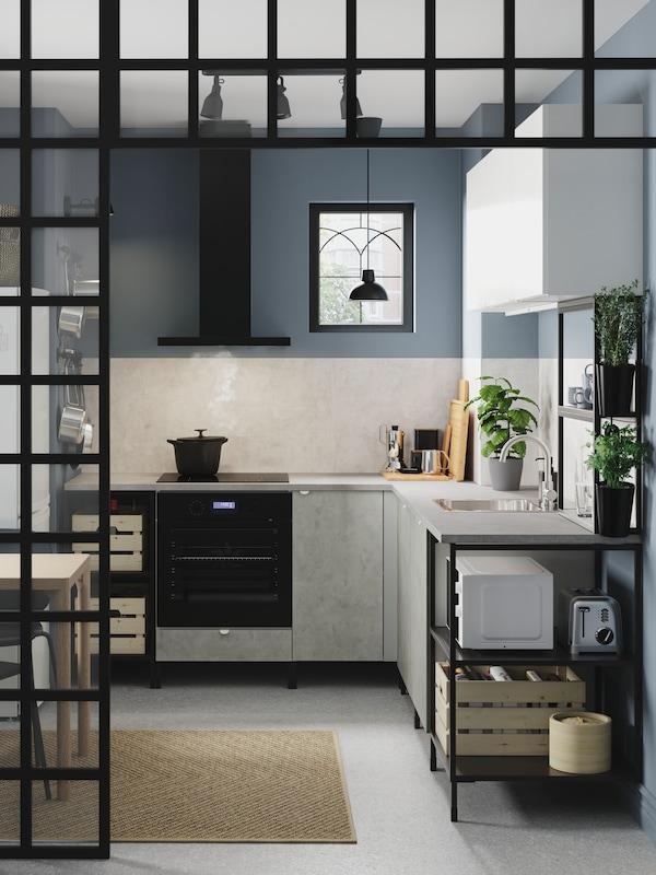 En ENHET kökskombination med stomme i antracit och grå fronter, dämpade blå väggar och en jutematta.