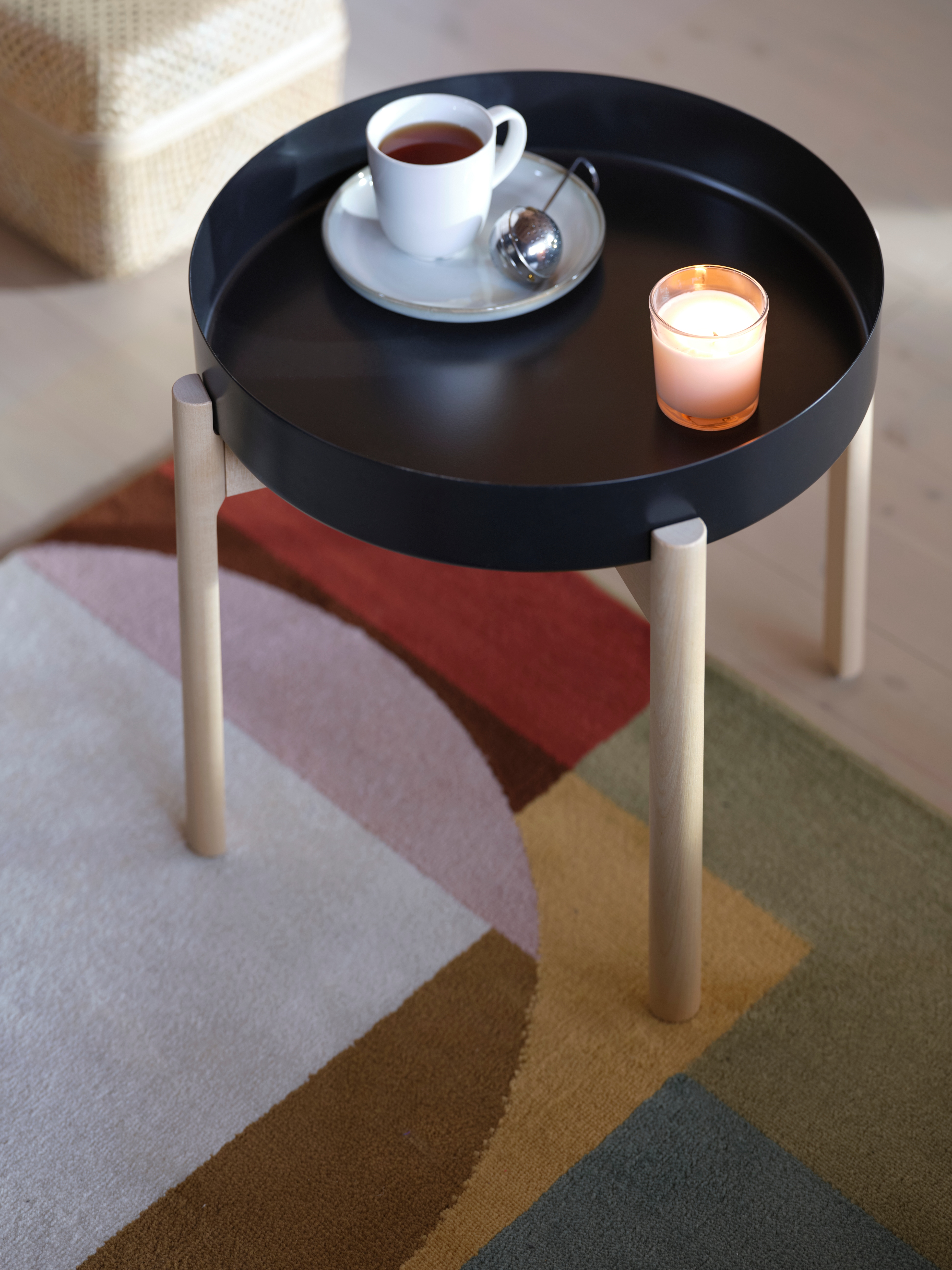 A multicoloured rug with a geometrical pattern, a black YPPERLIG coffee table with birch legs, a cup of tea and a candle.