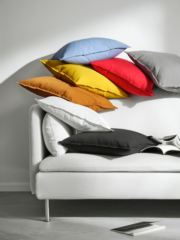 One end of a white sofa that has lots of cushions scattered on top of it, covered with different colour GURLI covers.