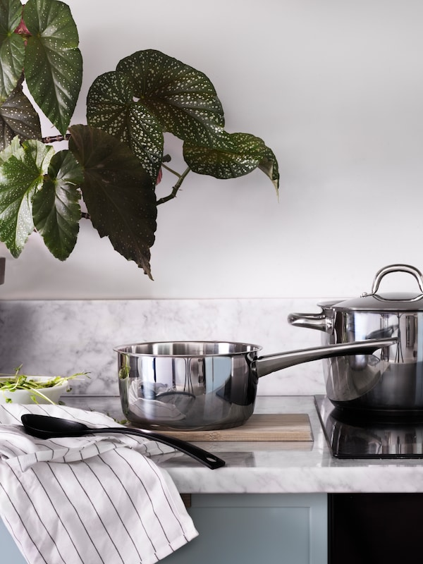 A stainless-steel saucepan standing in front of a matching pot on a marble worktop with a marble backsplash.