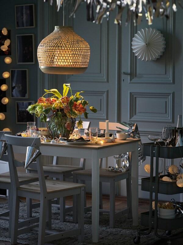 LERHAMN bord dukat med porslin och blommor för en festmåltid, med RÅSKOG rullvagn vid sidan om.