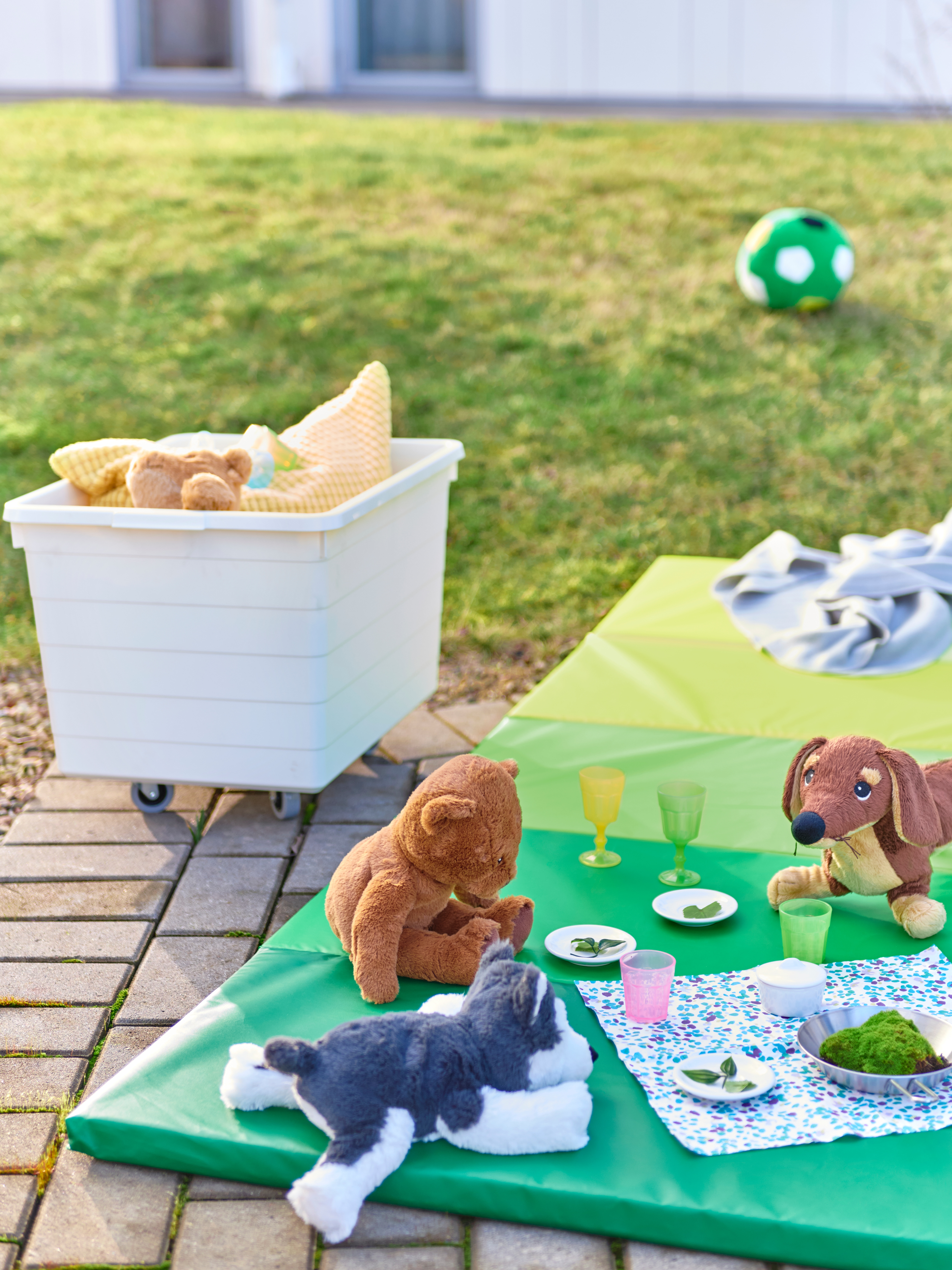 Soft toy animals have a pretend meal on a green PLUFSIG folding gym mat on a brick area by a box of toys on some grass.