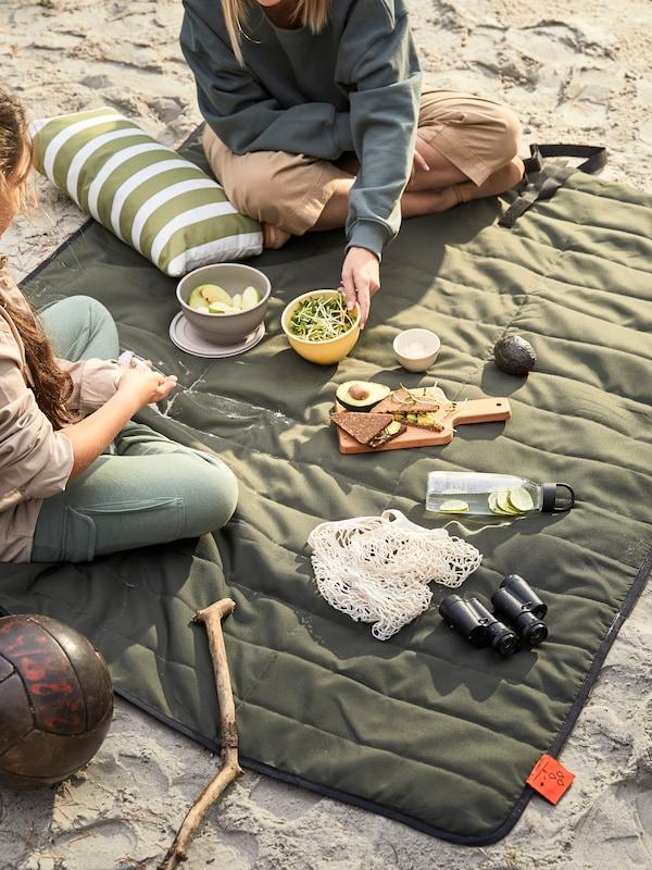 Piknik rannalla ruoan ja muiden tavaroiden kanssa, mukaan lukien kiikarit, FJÄLLMOT-piknikviltillä.