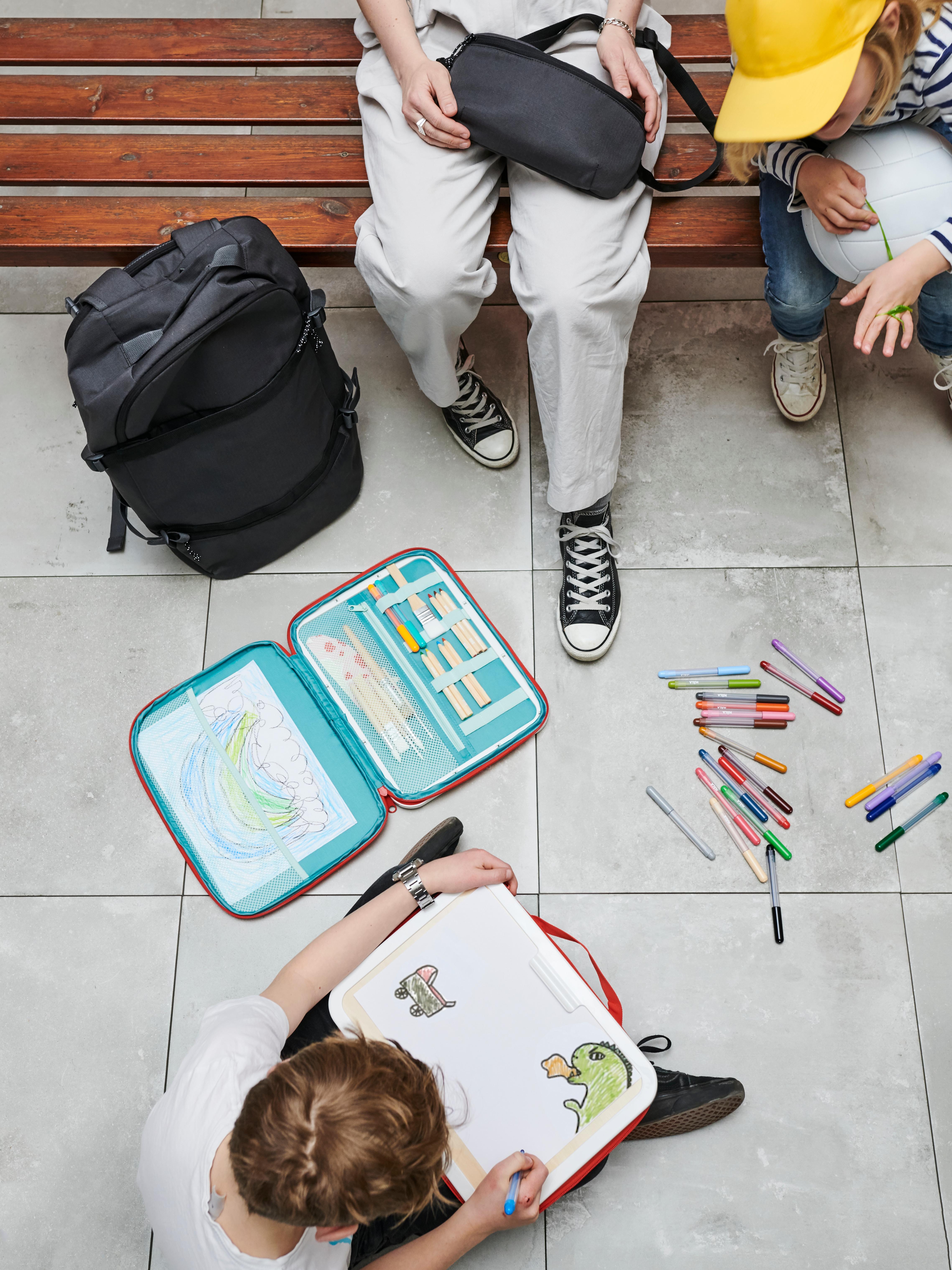 MÅLA/モーラ ポータブルお絵描きケースでお絵描きしている男の子。床に散らばったペン、バックパック。ベンチに座っている人2名。