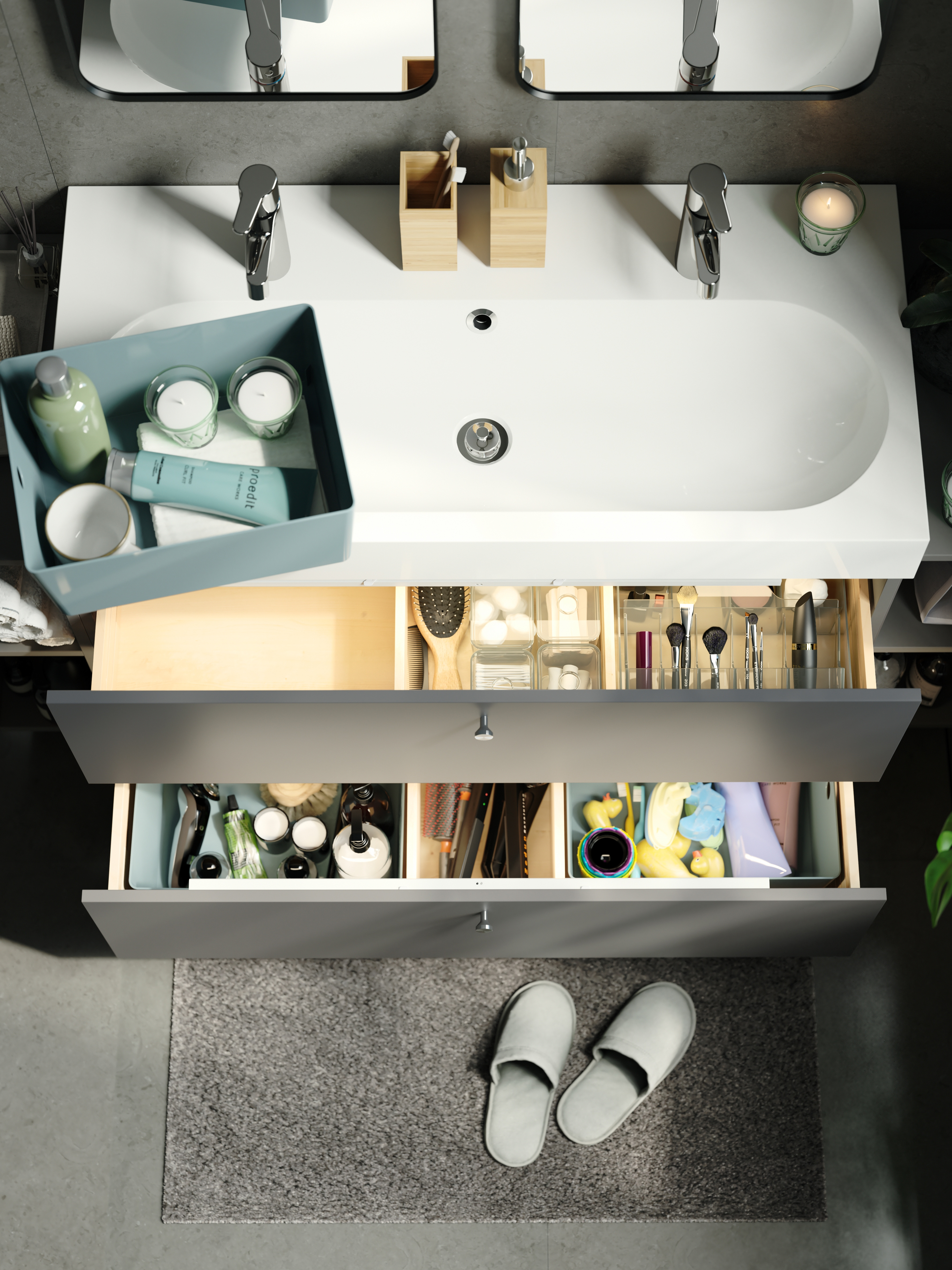 Open drawers of a washstand containing a smoked GODMORGON box with compartments and green storage boxes with toiletries.