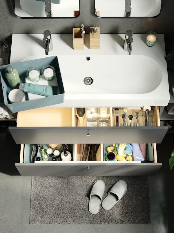 Tiroirs d'un meuble lavabo ouverts, révélant une boîte à compartiment GODMORGON fumée et des boîtes de rangement vertes contenant des articles de soins.