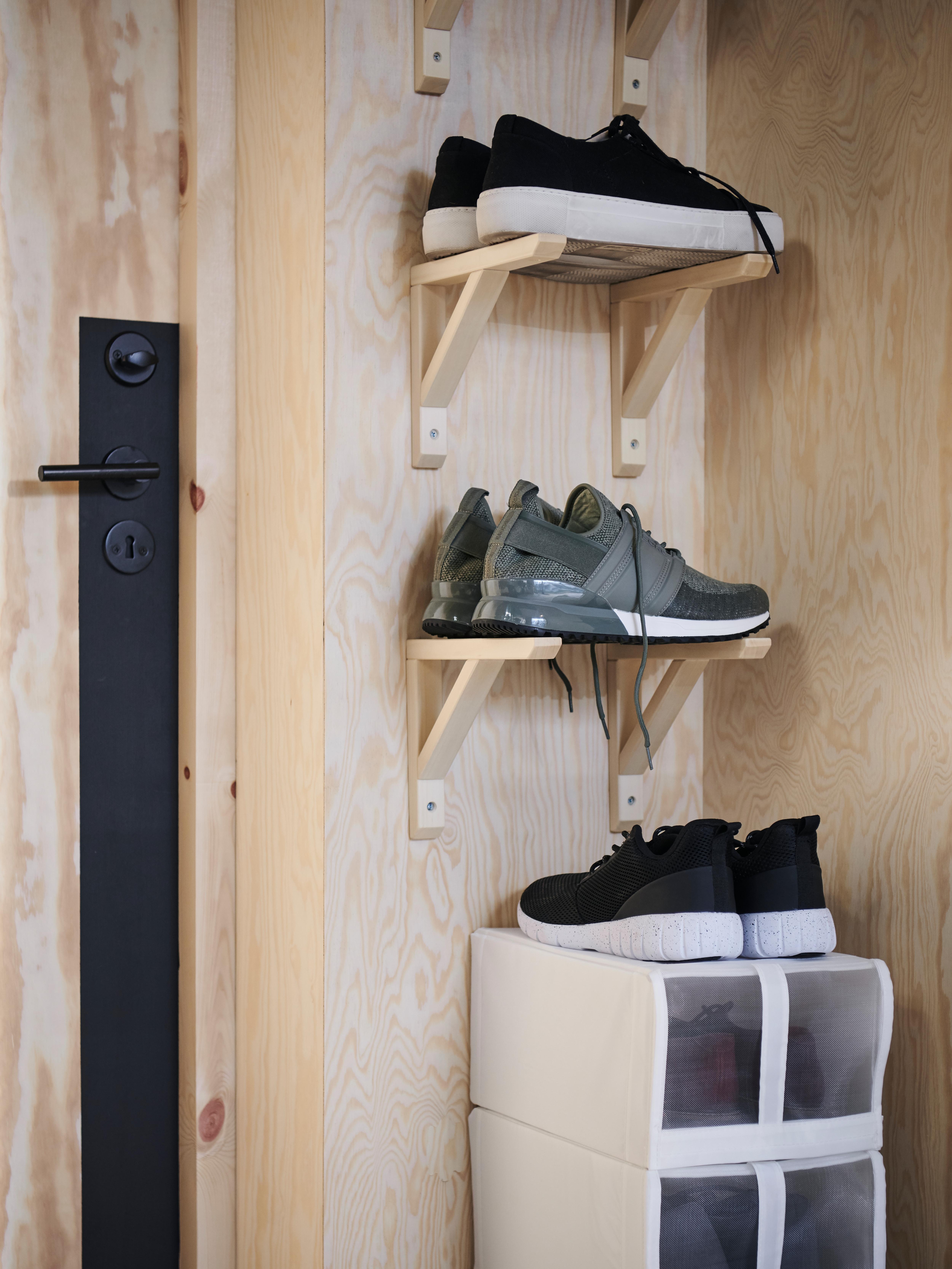 Mali zid pored vrata ima sportske cipele koje stoje na SANDSHULT nosaču od drva jasike, iznad hrpe bijelih kutija za cipele.