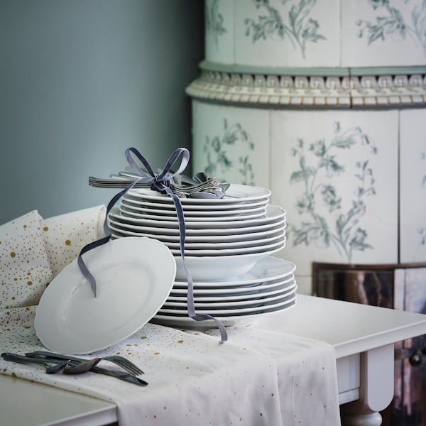 White UPPLAGA plates in all sizes, in a pile topped with cutlery tied together with a ribbon, on a table by a fireplace.