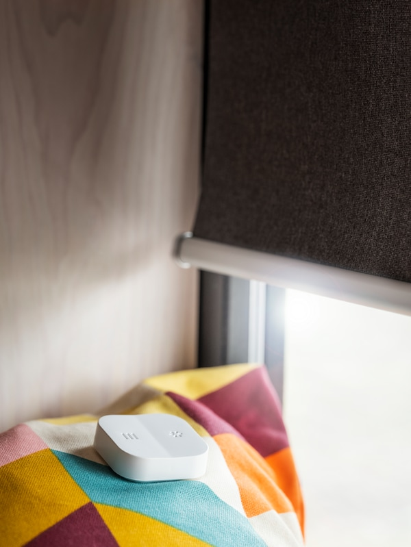 A remote control for a roller blind sits on a multicolored blanket in front of a window with the roller blind.