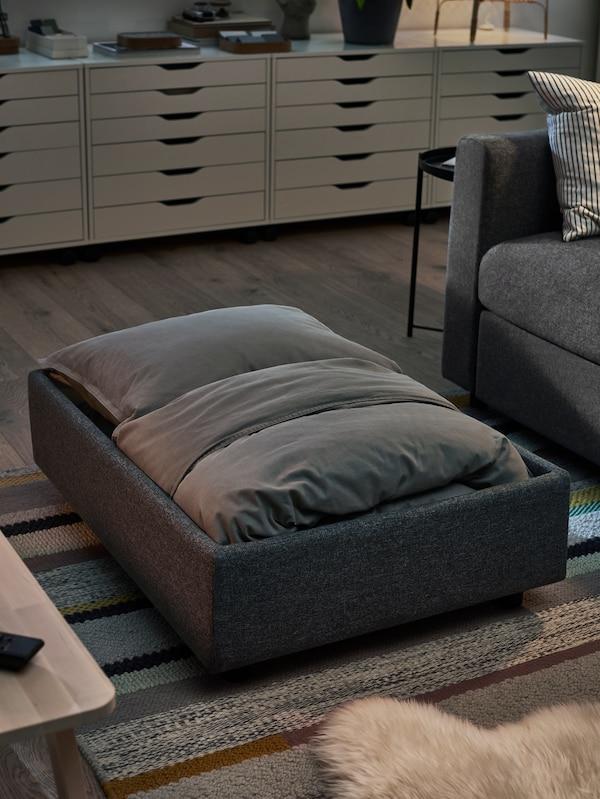 Sängkläder förvaras i en fotpall med klädsel i GUNNARED mellangrå och ALEX hurtsar med lådor i bakgrunden.