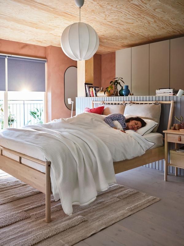 Persona dormida en una cama BJÖRKSNÄS con ropa de cama BJÖRKSNÄS en blanco. Hay una lámpara de techo y libros sobre un estante detrás de la cama.