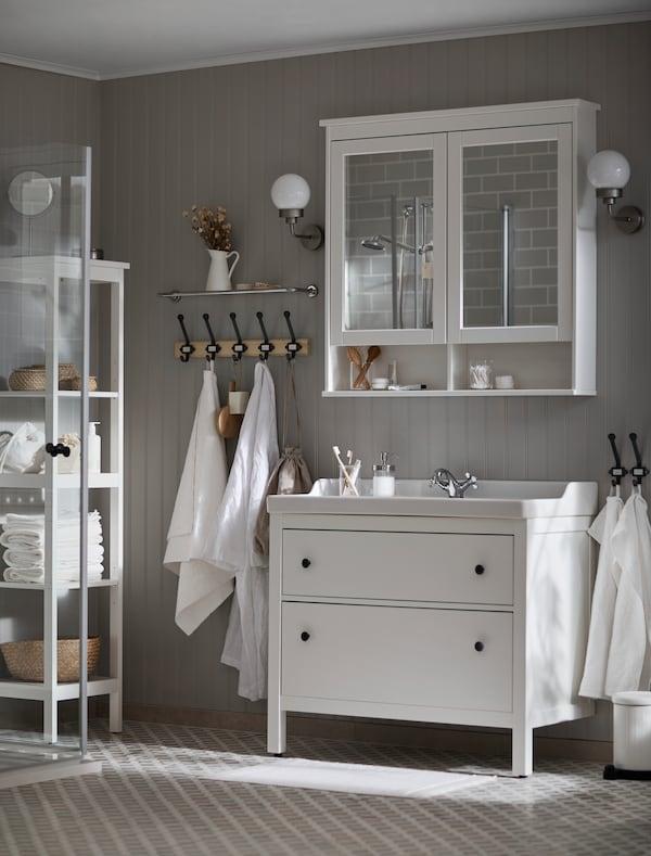 Une salle de bains blanche et lumineuse où se trouvent un meuble pour lavabo HEMNES et une armoire à pharmacie. Des serviettes blanches suspendues à des crochets sur un mur gris.