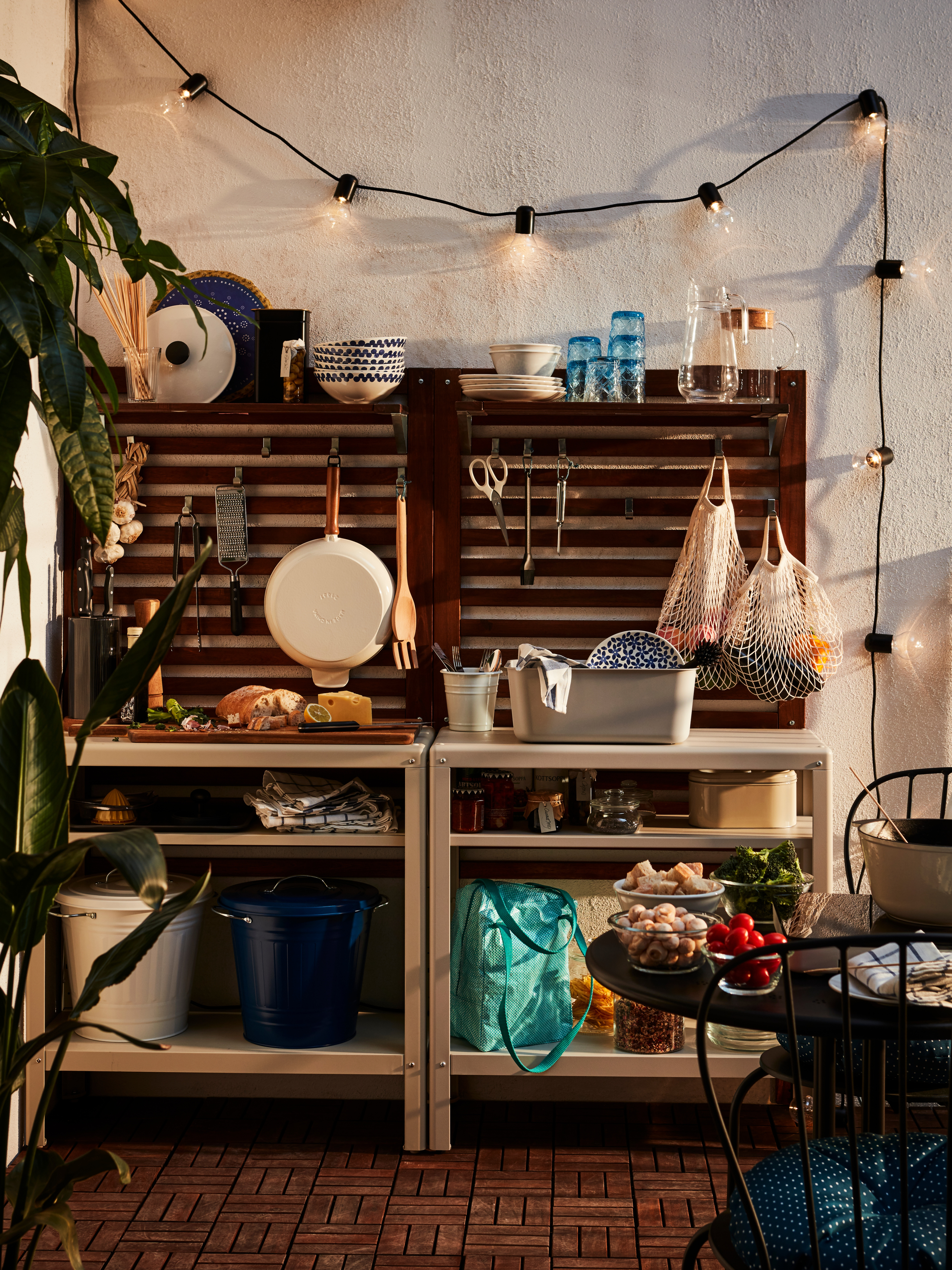 KOLBJÖRN indoor/outdoor shelving unit on a patio with outdoor gardening and dining items on its steel shelves and worktop.