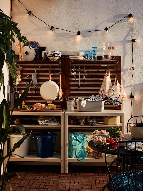Két asztal különböző tárgyakkal, például kosarakkal, táskákkal, dobozokkal és egy vágódeszkával, egy polc előtt.