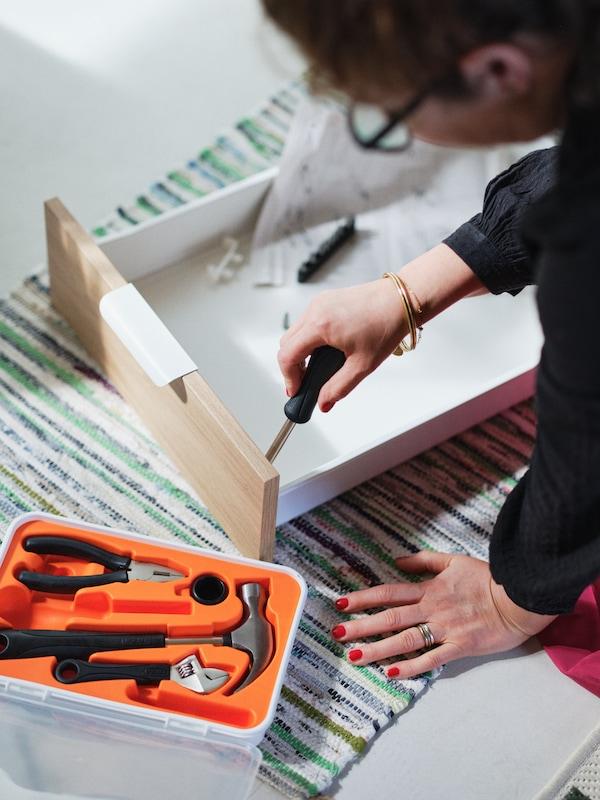 한 여성이 바닥에 앉아서 FIXA 픽사 17종 공구 세트의 스크루드라이버를 사용해 서랍을 조립하는 모습.