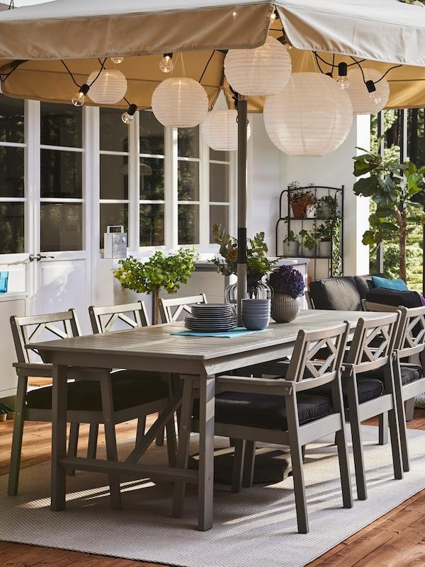 En terrasse med et stor og gråt havebord af træ med seks stole rundt om i samme stil med armlæn og mørkeblå hynder. Der er en parasol slået op hvori der hænger LED-lamper, der ligner rispapirlamper.