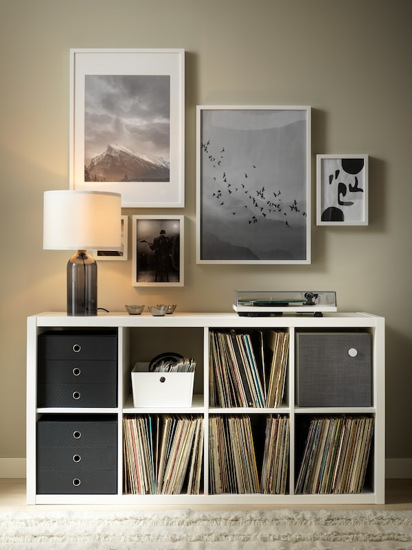 A TONVIS table lamp and a record player standing on a white KALLAX shelving unit. Framed art hangs on the wall above.