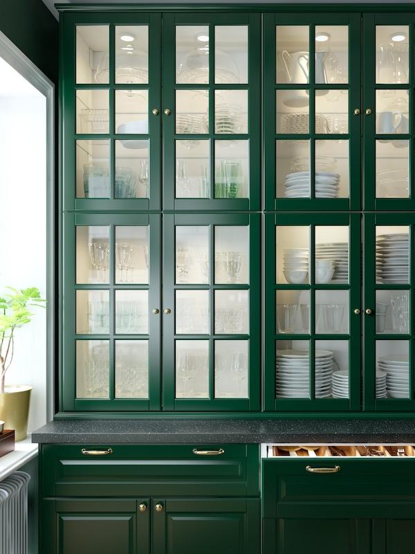 Otto pensili con ante in vetro verde scuro e dettagli smussati. Articoli per la tavola sono conservati all'interno di mobili illuminati.