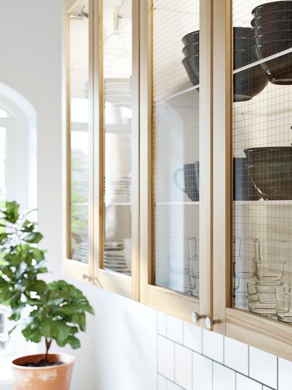 Veggskap med TORHAMN dører i ask og vitrinedører inneholder dekketøy.