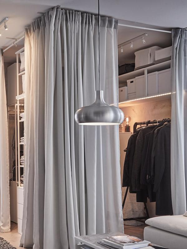 Otvoreni garderober, svetlosive GUNRID zavese, crna šipka za odeću i VÄXJÖ aluminijumska šarena visilica..